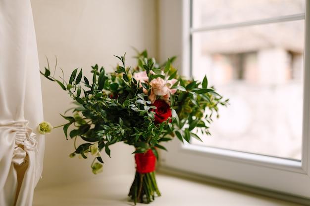 흰색 꽃과 빨간색의 새싹이 피지 않는 빨간색과 분홍색 장미 회양목 가지의 신부 부케