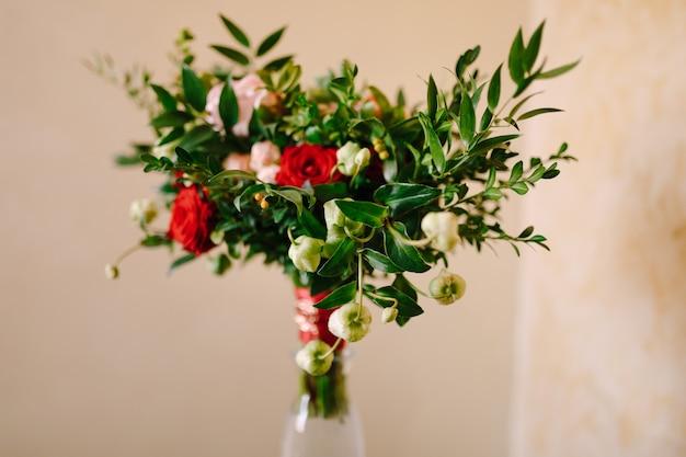 흰색 꽃의 꽃 봉오리가 피지 않는 빨간색과 분홍색 장미 회양목 가지의 신부 부케