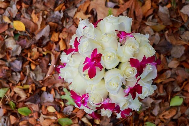 나무 판자에 장미의 신부 부케 잎의 배경에 흰색 장미의 신부 부케