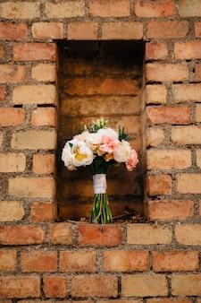 Букет невесты из белых и розовых пионов эрингиума и зеленых бутонов с белыми лентами на кирпиче