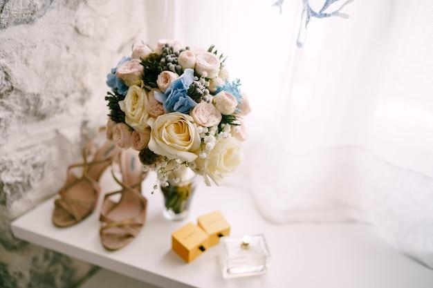 白とピンクのバラの赤ちゃんのブライダルブーケは、レンガの中でマツムシソウと白いリボンを呼吸します