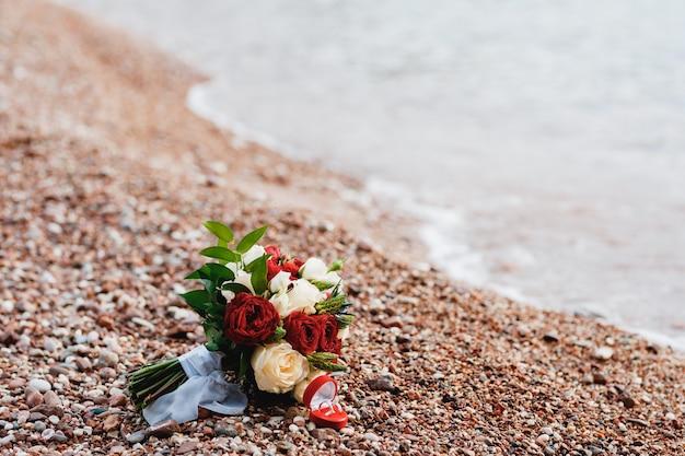 해변에 흰색 리본이 달린 흰색 읽기 및 크림 장미 ornithogalum eryngium의 신부 부케