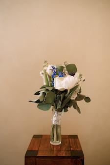 흰색 튤립 델피니움 살랄 리모늄과 레이스 리본을 유리 꽃병에 넣은 신부 부케