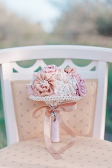 Bridal bouquet of pink artificial flowers lies on a pink elegant vintage chair on a blurred garden background, selective focus