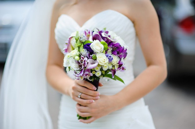 Bridal bouquet of purple and white flowers in hands of the bride