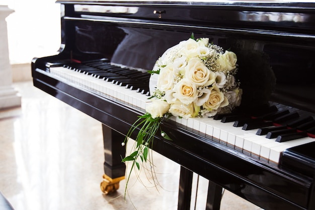 Bridal bouquet of rose resting on the keys of a black piano