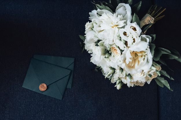 Bridal bouquet on the sofa next to the invitation