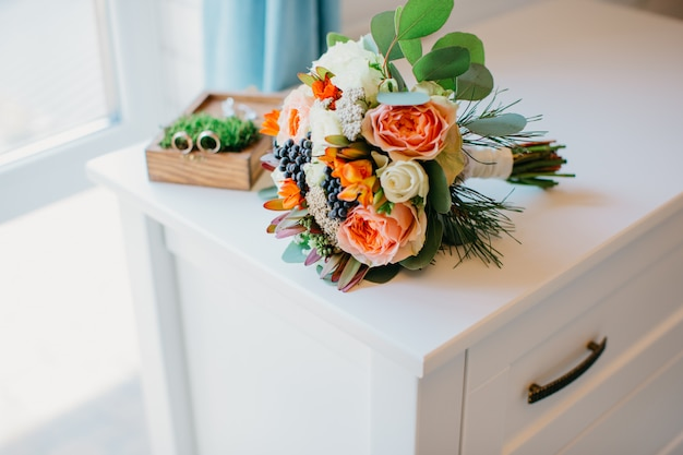 Bridal bouquet of white and orange flowers on a white table.