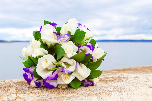 Bridal bouquet of white rose in bright colors with purple eustoma against the lake