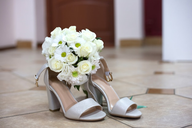 Bridal bouquet of white roses lies on the wedding sandals