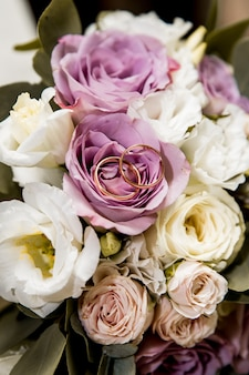 Bridal bouquet with purple and white flowers and rings