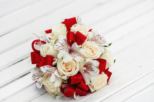 Bridal bouquet with red ribbons, beige roses and orchids