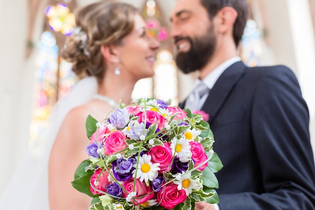 Bridal couple in church with flower bouquet