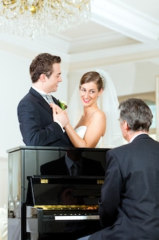 Bridal couple in front of a piano