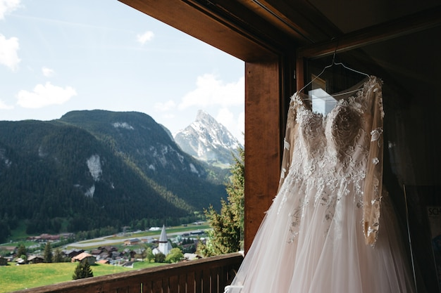 Bridal dress hangs on a hanger on a window with a mountains view