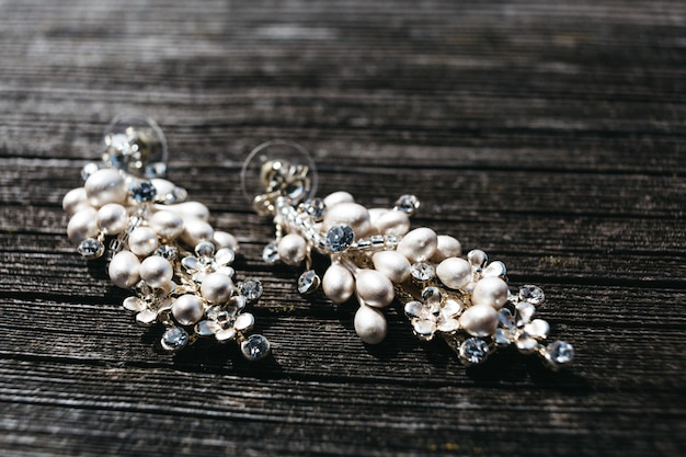 Bridal earrings lie on wooden surface