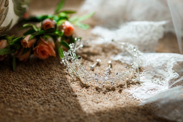 Bridal jewelry lying near veil with lace and flowers