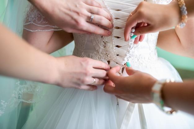 신부의 아침, 신부는 드레스를 입는다. 옷 입기, 웨딩 드레스, 후면보기 버튼 조정. 클로즈업, 자르기.