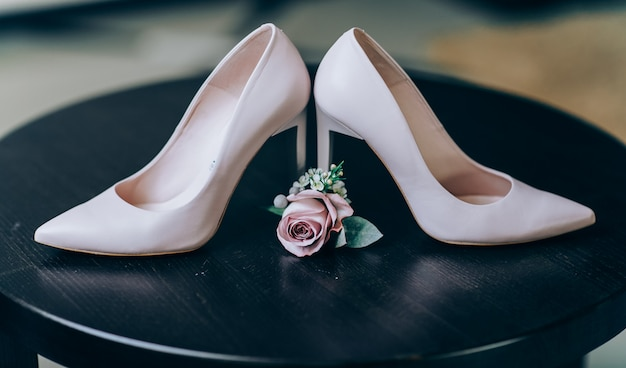 Bridal morning details composition. wedding bouquet of pink flowers, boutonniere and leather shoes