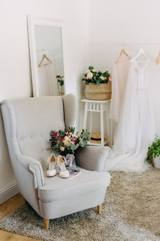 Bridal morning at home. bridal shoes, bouquet and wedding dress indoors.