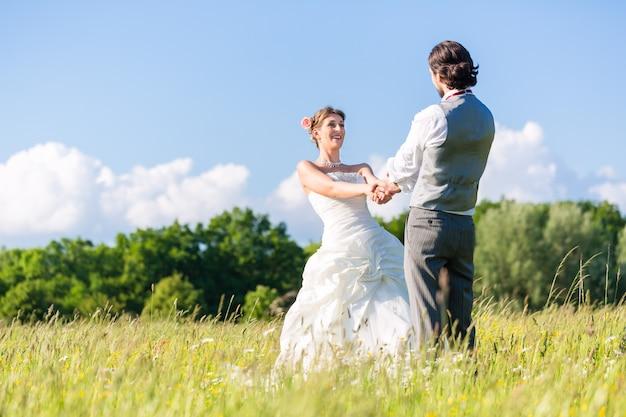 Bridal pair dancing on field celebrating