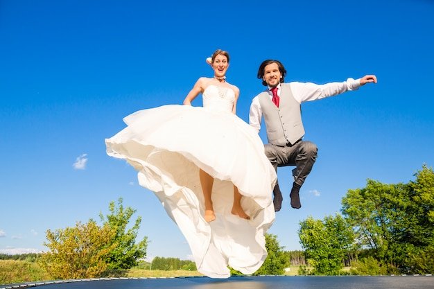 Bridal pair jumping outside on trampoline