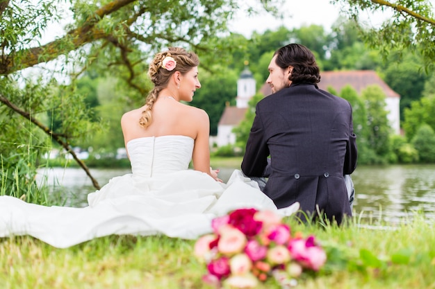 Bridal pair with bouquet sitting on meadow