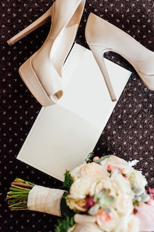 Bridal shoes and bouquet with invitation