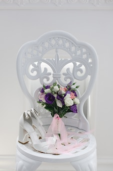 Bridal shoes on a white chair indoor in the stylish interior