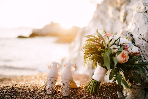 Bridal shoes with rhinestones on heels standing on the sea pebble beach next to a bridal bouquet