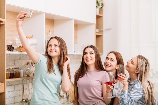 ブライダルシャワーのお祝い。ホームパーティーの楽しみ。自撮りをしている興奮した若い女性。グラスに赤ワイン。