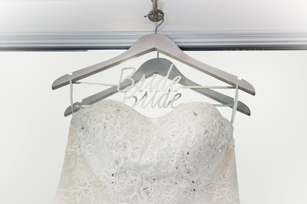 Bridal wedding dress on a hanger with bride written on hit, in front of a mirror