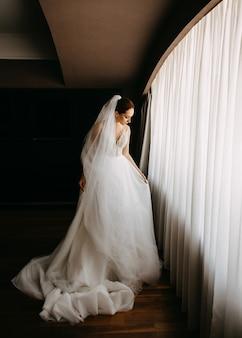 花嫁は彼女のドレスを調整し、窓の光の中に立っています。