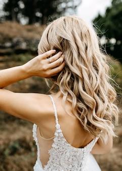 婚約指輪を身に着けて、ウェーブのかかった髪を調整する花嫁