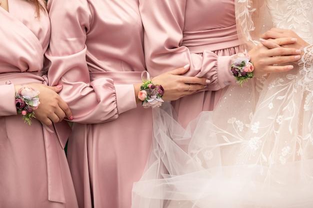 花嫁とブライドメイドの結婚式の日に手を繋いでいるピンクのドレス