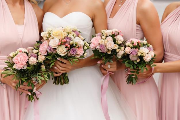 結婚式の日に花束でポーズピンクのドレスで花嫁とブライドメイド