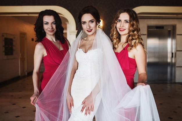 Невеста и подружки невесты в красных платьях стоят в зале гостиницы