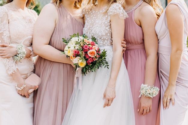 パステルピンクの色調のチュールマキシドレスを着ている花嫁とブライドメイド