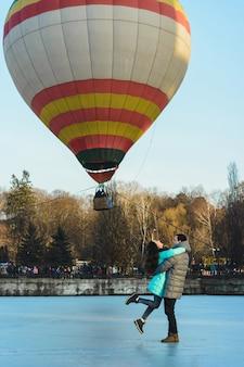 얼어 붙은 호수와 도시 공원에서 비행하는 풍선의 배경에 대해 신랑과 신부.