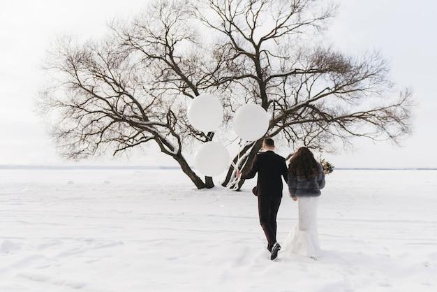 Жених и невеста среди снежного пейзажа с большими белыми воздушными шарами