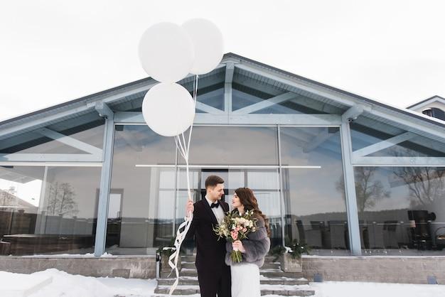 Жених и невеста среди снежного пейзажа с белыми большими воздушными шарами