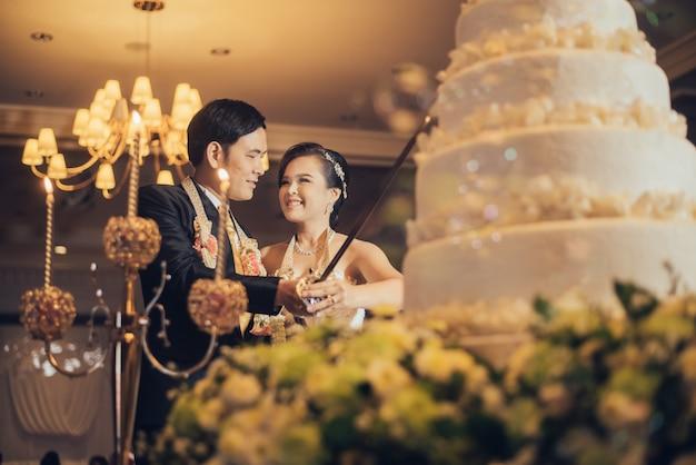 新郎新婦は結婚式の日にお祝いのケーキを切っています。