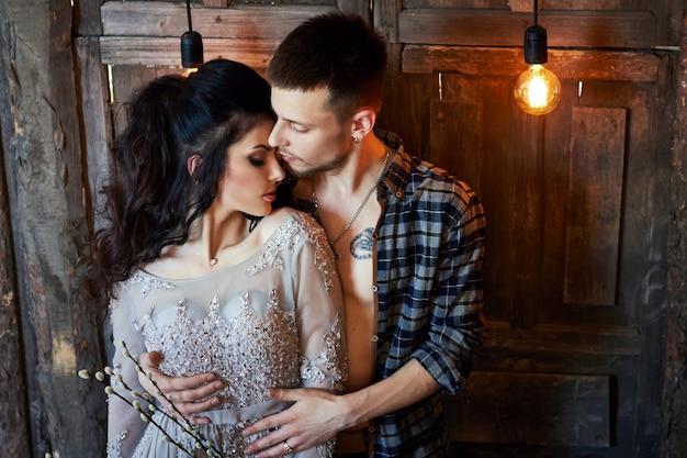 新郎新婦は朝、結婚式の準備をしています。家で抱き締める愛情のあるカップル。ハンサムな新郎と魅力的な花嫁。カップルは結婚式の準備をします