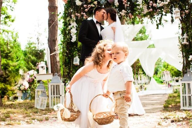 Жених и невеста целуются после свадебной церемонии. очаровательные дети с летающими лепестками роз в корзинах