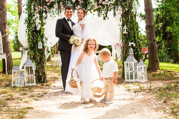 Жених и невеста улыбаются после свадебной церемонии. очаровательные дети с летающими лепестками роз в корзинах