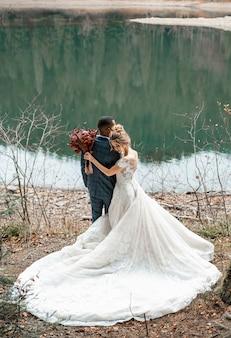 美しい湖での結婚式で新郎新婦。