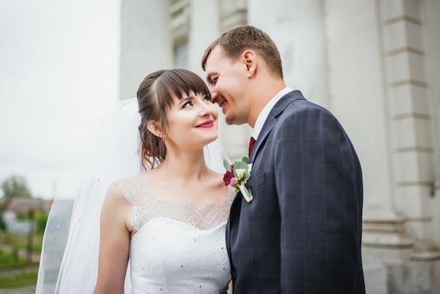 Жених и невеста на свадьбе день прогулки на открытом воздухе возле архитектуры.