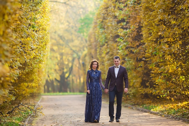 秋の自然に屋外を歩く日の結婚式で新郎新婦