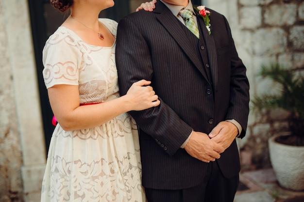 春の自然の中で屋外を歩く結婚式の日の新郎新婦。ブライダルカップル、緑豊かな公園で抱きしめる幸せな新婚の女性と男性。屋外の愛情のある結婚式のカップル。新郎新婦