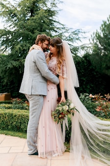 春の自然の屋外歩行の日の結婚式で新郎新婦。幸せな新婚女と緑豊かな公園を受け入れる男。結婚式のカップルを愛してください。